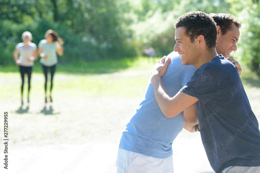 Fototapeta two young sportmen giving eachother a hug