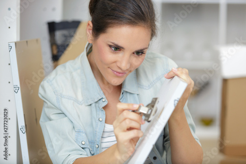 Photo  determined woman assembling kitchen cupboard