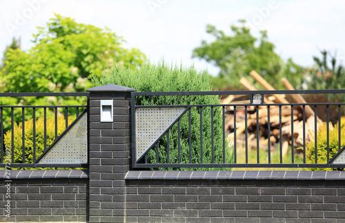 Ogrodzenia, murowane ogrodzenie z cegły i stali, zielone drzewa.
