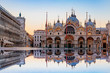 Sunrise in San Marco square with Campanile and San Marco's Basilica. The main square of the old town. Venice, Veneto Italy. Reflection on the flooded square.