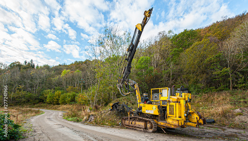 A drilling rig by a dirt road.
