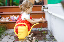 A Little Girl Dressed In A Sundress Holds Her Hands Under Running Tap Water Sitting Next To The Watering Can In The Garden Next To The House On The Summer Day