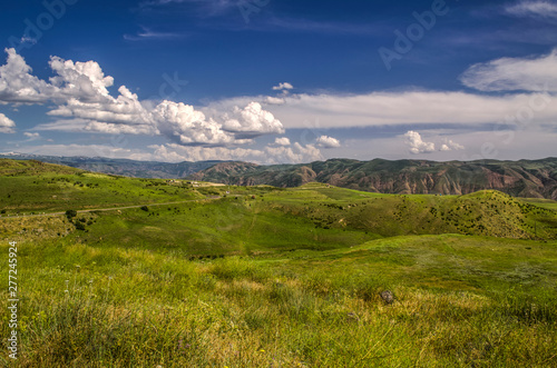 Fototapeta View of the highway with a turn leading to the Garni temple among the mountains of Geghama ridge in Armenia against the blue sky covered with huge clouds obraz na płótnie