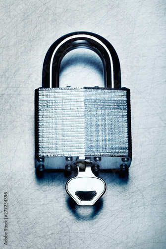 Fotografie, Obraz  High security steel padlock with key on scratched steel surface