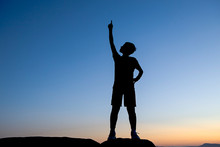 Silhouette Of Boy Pointing To The Sky.