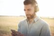canvas print picture - Junger Mann mit Kopfhörer hört Musik über das Smartphone