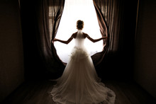 The Bride In A Wedding Dress With A Train Opens The Curtains Of The Window, Stands Back, You Can See Her Silhouette, Against The Light