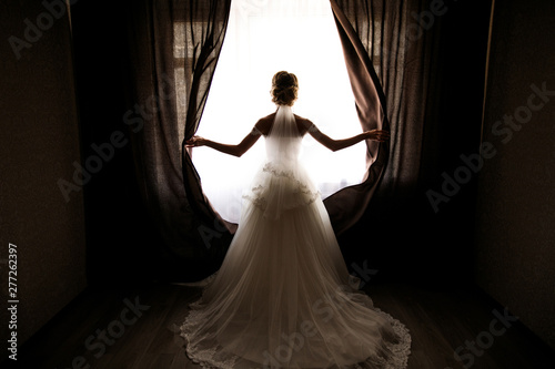 the bride in a wedding dress with a train opens the curtains of the window, stan Fototapete