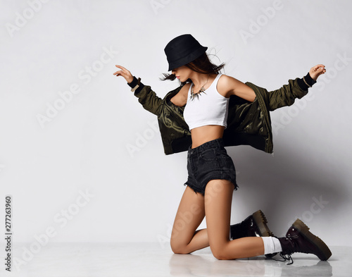 Cuadros en Lienzo Young beautiful hipster girl sitting on her knees full body in shorts brown spri