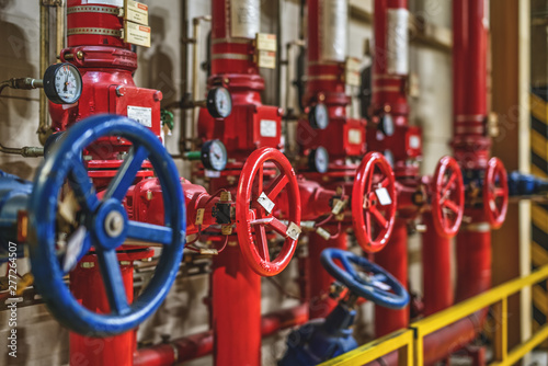 blue and red valves on the background of pipes in the production room Canvas Print