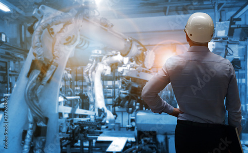 Photo production engineer  with automate wireless Robot arm in smart factory background