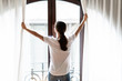 Young happy woman opening window curtains at home