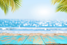 Top Of Wood Table With Seascape And Palm Leaves, Blur Bokeh Light Of Calm Sea And Sky At Tropical Beach Background. Empty Ready For Your Product Display Montage.  Summer Vacation Background Concept.