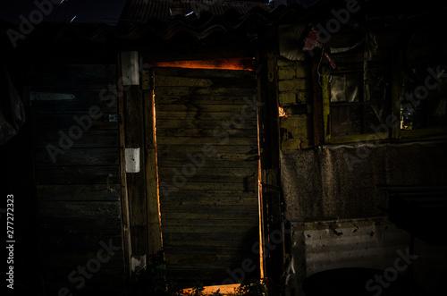 Close up view of old antique wooden door inside a dark room. Selective focus.