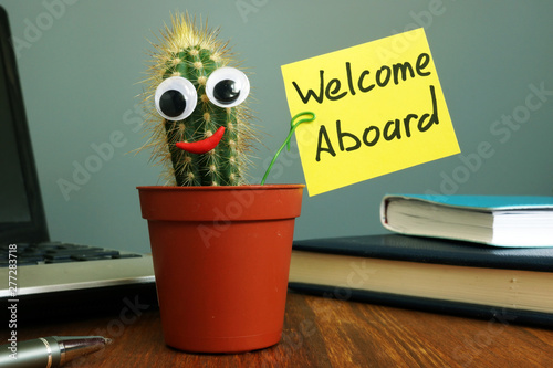 Welcome aboard concept. Funny cactus on workplace in the office. Wallpaper Mural