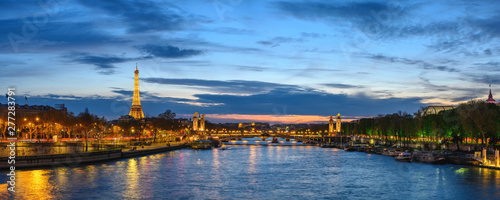 Paris France panorama city skyline night at Seine River with Pont Alexandre III bridge and Eiffel Tower