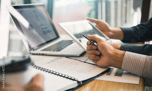 Photo Business partnership coworkers using a tablet to chart company financial statements report and profits work progress and planning in office room