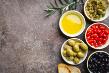 Italian Appetizer From Above. Mediterranean Snack Assortment. Black And Green Olives, Capers, Olive Oil, Onion, Pepper And Garlic Top View.