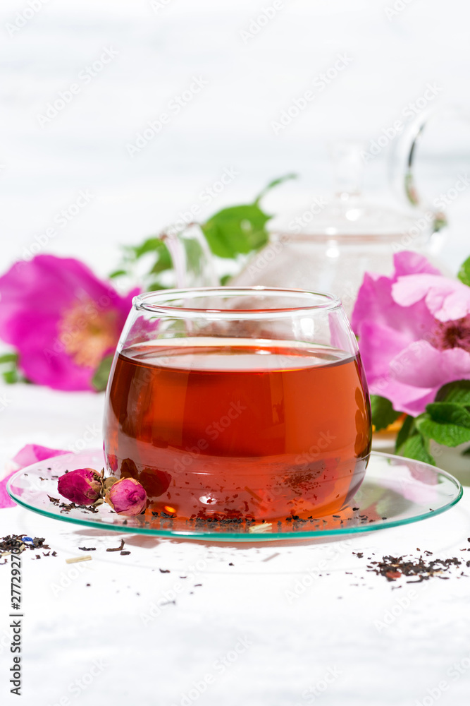 Fototapety, obrazy: fragrant tea with wild rose in a glass cup on a white background, vertical