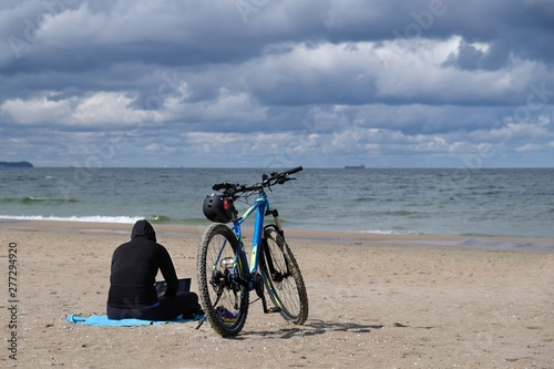 Foto op Plexiglas Poland, Gdansk, Baltic Sea - women in black cloth sitting on the beach with bike in cloudy day with amazing dramatic clouds