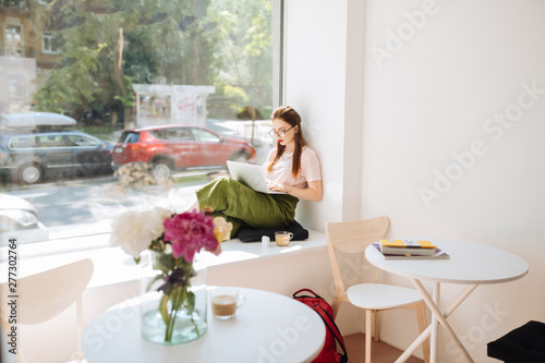Poster Individuel Relaxed longhaired girl leaning on wall during work