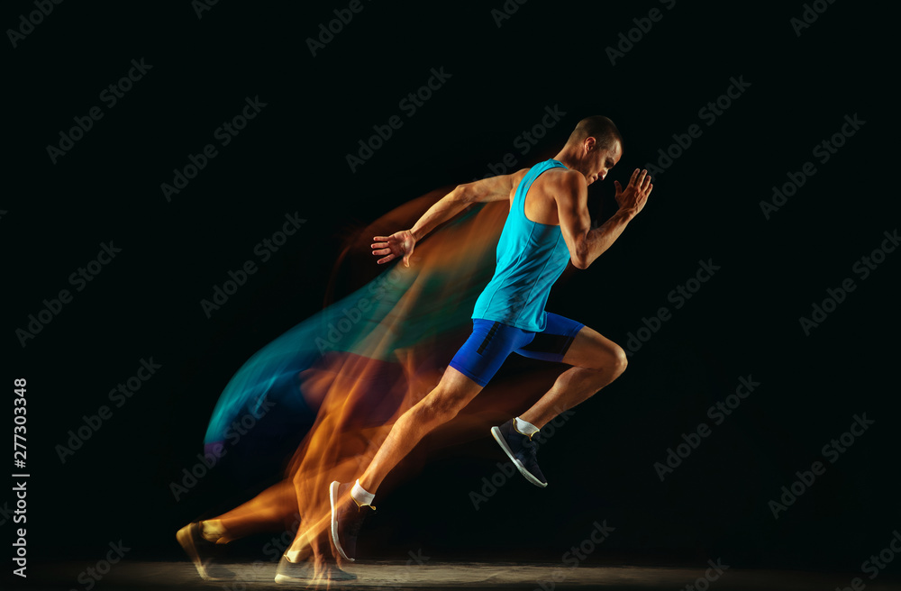 Fototapety, obrazy: Professional male runner training isolated on black studio background in mixed light. Man in sportsuit practicing in run or jogging. Healthy lifestyle, sport, workout, motion and action concept.