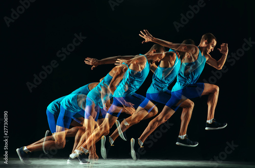 Professional male runner training isolated on black studio background in mixed light. Man in sportsuit practicing in run or jogging. Healthy lifestyle, sport, workout, motion and action concept. - fototapety na wymiar