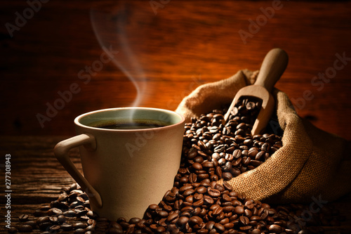Keuken foto achterwand Cafe Cup of coffee with smoke and coffee beans on old wooden background