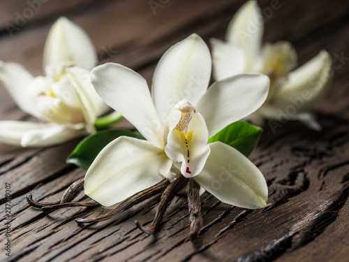 Autocollant pour porte Orchidée Dried vanilla sticks and vanilla orchid on wooden table.