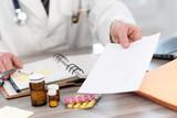 Fototapeta Kawa jest smaczna - Hand of doctor giving a prescription