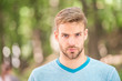 Charming confidence. Blond man. Man with unshaved mustache and beard hair with stylish haircut. Handsome man in casual tshirt on blurred natural background. Caucasian man on summer day