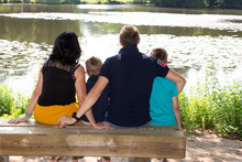 Family Of Four People Mother Father And Brothers Children Boys Sitting On Lake Wooden Bench
