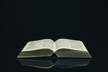 Open Holy Bible On A Black Glass Table Dark Background