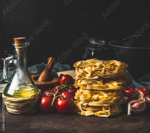 Italian pasta with tomatoes, olives oil and garlic on dark rustic kitchen counter at dark background Fototapeta