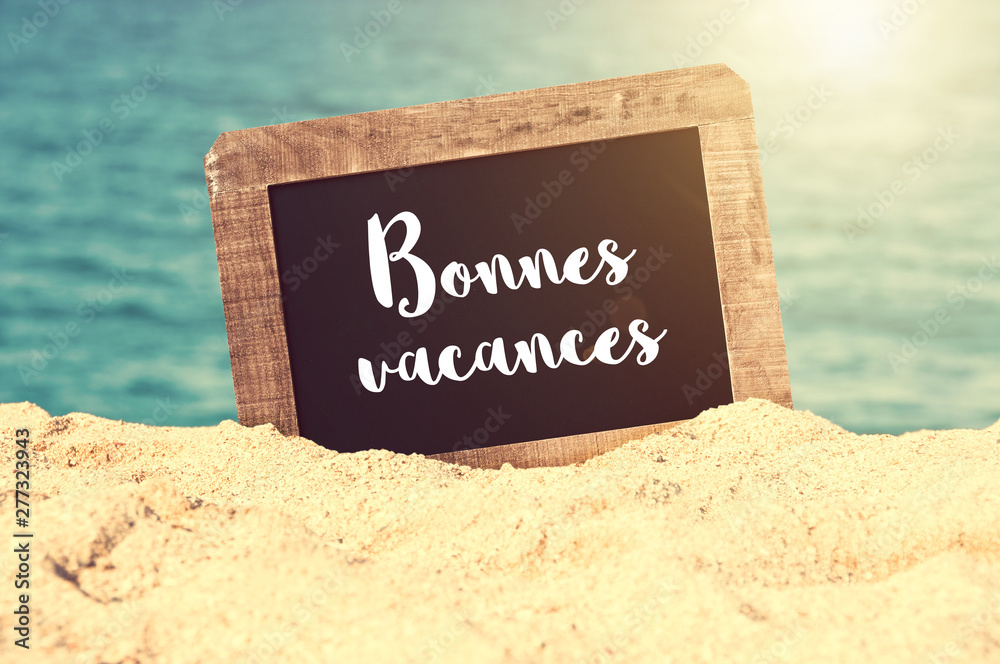 Fototapety, obrazy: Bonnes vacances (meaning Happy holiday in French) written on a vintage chalkboard in the sand of a beach