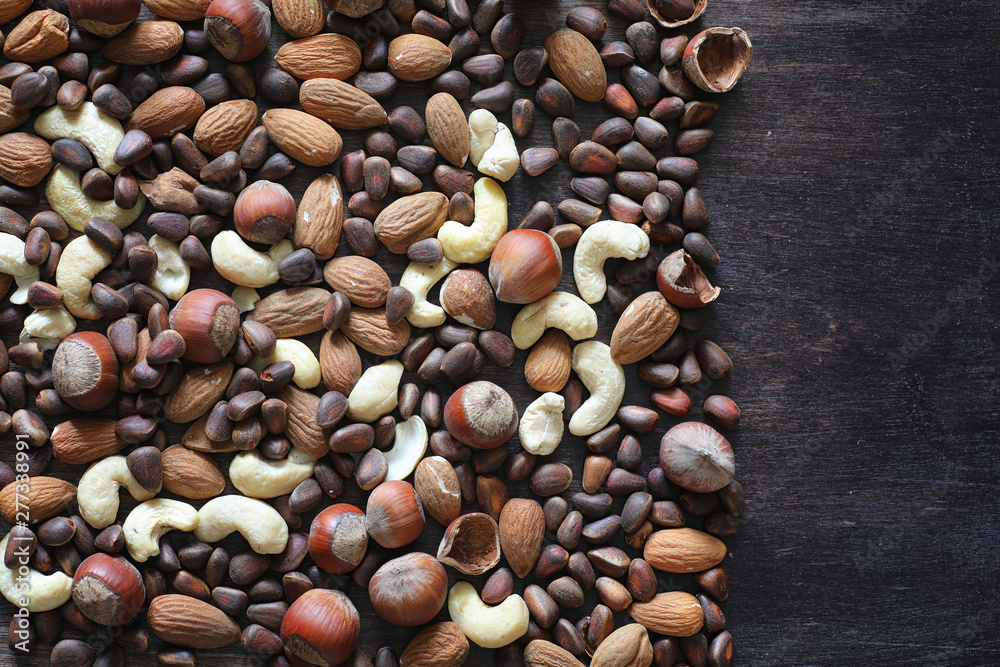 Fototapety, obrazy: Different nuts on a wooden table. Cedar, cashew, hazelnut, walnuts and a spoon on the table. Many nuts are inshell and chistchenyh on a wooden background.