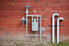 Natural Gas Meter Gauge And Pipeline On The Red Brick Wall With Copy Space
