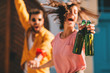 canvas print picture Young couple dancing on the street and holding two bottles of beer. Selective focus on beer.