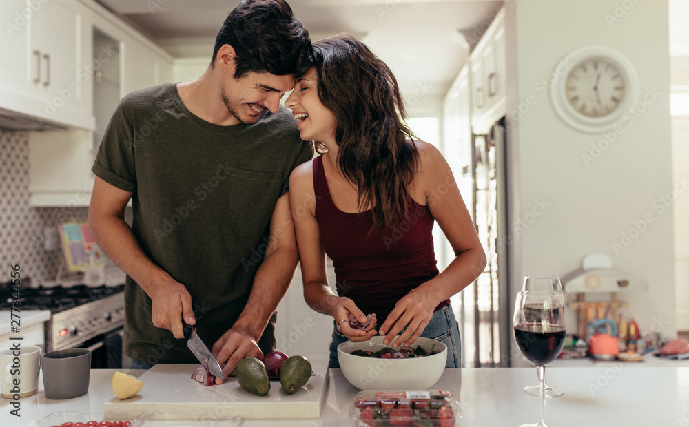 Fototapety, obrazy: Loving couple cutting vegetables together in kitchen