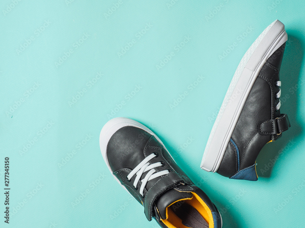 Fototapety, obrazy: pair of new kids or adult sneakers on blue background, top view. Flat lay gray and yellow or mustard color sneakers shoes on colorful bright blue background with copy space for text or design
