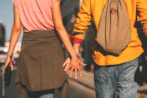 Fényképezés  Young couple holding hands while going to a music festival