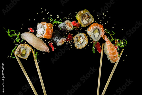 obraz PCV Seamless pattern with sushi. Food abstract background. Flying sushi, sashimi and rolls isolated on the black background.