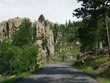 Scenic drive along a winding road with dramatic granite formations at Needles Highway in South Dakota.