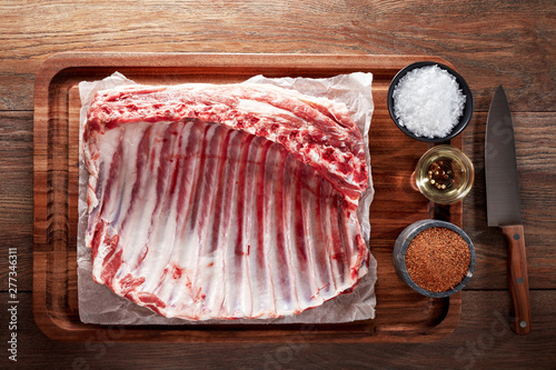 Foto Raw rack of lamb ribs on white cooking paper and wooden cutting table