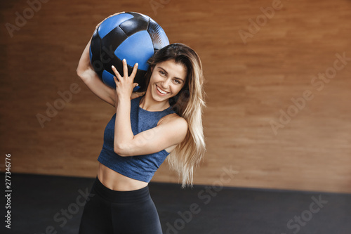 Happy cheerful strong sportswoman with abdominal muscles, carry crossfit medi...