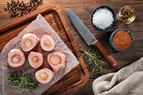Fototapeta Raw calf bones on white cooking paper and wooden cutting table