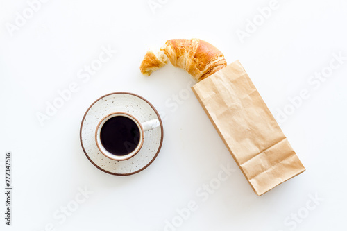 Stampa su Tela Breakfast with croissant in paper bag and cup of coffee on white background top