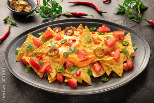 Fotomural Mexican nachos with a cheese sauce, chili and jalapeno peppers, tomatoes, and ci