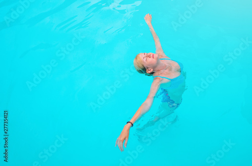Foto op Aluminium Flamingo Caucasian girl in a blue swimsuit in the pool. Head up, eyes closed. The concept of summer holidays, travel, relaxation, enjoyment of warmth. Rest in tropical countries, exotic, resort.Place for text.