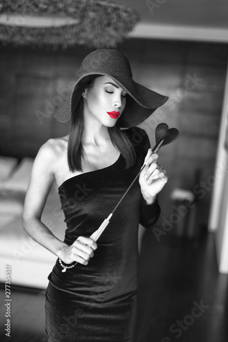 Fotografia Sexy dominant woman in hat and red lips holding whip indoors selective coloring